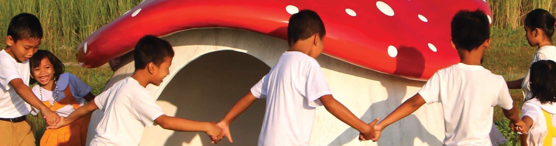 Children playing around mushroom cubby house